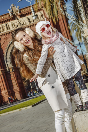 in Barcelona for a perfect winter. cheerful modern mother and daughter in Barcelona, Spain