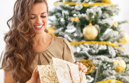 Happy young woman looking into shopping bag near christmas tree 스톡 콘텐츠
