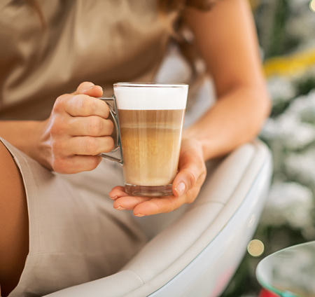 macchiato: Closeup on latte macchiato in hand of woman in front of christmas tree Stock Photo