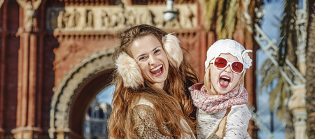 in Barcelona for a perfect winter. Portrait of cheerful modern mother and daughter near Arc de Triomf in Barcelona, Spain