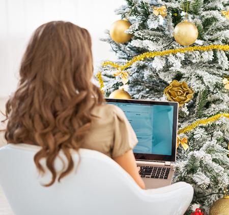 Woman using laptop near christmas tree . rear view