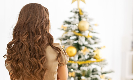 Young woman standing in front of christmas tree . rear view Stock Photo