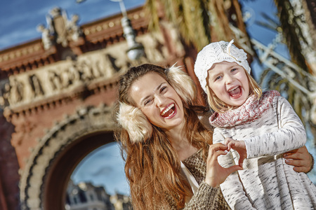 in Barcelona for a perfect winter. smiling young mother and child in Barcelona, Spain showing heart shaped hands Stock Photo