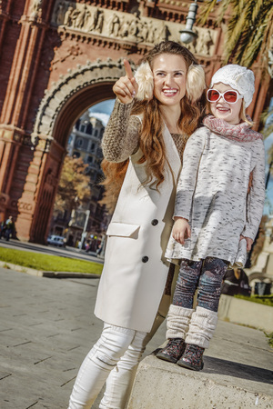 in Barcelona for a perfect winter. Full length portrait of smiling modern mother and child near Arc de Triomf in Barcelona, Spain pointing on something Stock Photo