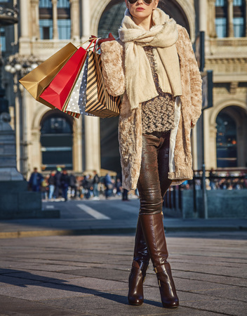 Rediscovering things everybody love in Milan. Closeup on trendy tourist woman with shopping bags near Galleria Vittorio Emanuele II in Milan, Italy looking into the distance