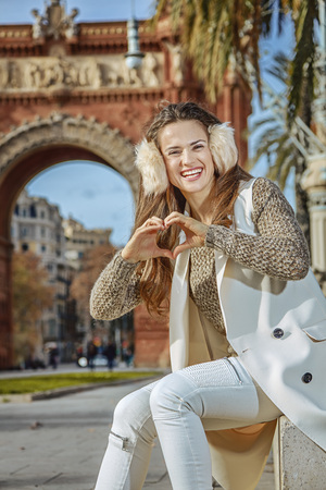 in Barcelona for a perfect winter. Portrait of happy modern fashion-monger in earmuffs in Barcelona, Spain showing heart shaped hands