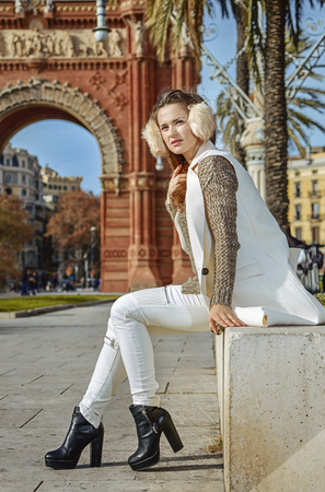 in Barcelona for a perfect winter. modern woman in earmuffs in Barcelona, Spain looking into the distance while sitting on a parapet