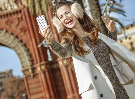 in Barcelona for a perfect winter. smiling elegant fashion-monger in earmuffs in Barcelona, Spain with mobile phone taking selfie and showing victory gesture