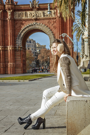 parapet: in Barcelona for a perfect winter. smiling trendy woman in earmuffs near Arc de Triomf in Barcelona, Spain looking into the distance while sitting on a parapet