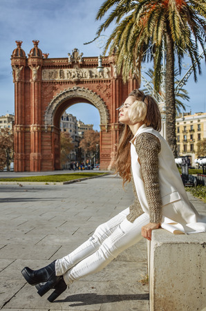 parapet: in Barcelona for a perfect winter. relaxed trendy fashion-monger in earmuffs near Arc de Triomf in Barcelona, Spain sitting on a parapet