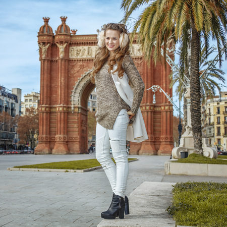 in Barcelona for a perfect winter. Full length portrait of happy young woman in earmuffs in Barcelona, Spain