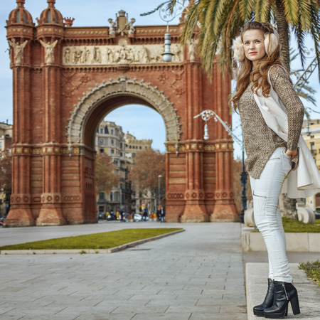 in Barcelona for a perfect winter. Full length portrait of young fashion-monger in earmuffs in Barcelona, Spain looking into the distance Stock Photo