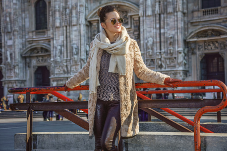 everybody: Rediscovering things everybody love in Milan. happy trendy woman in fur coat and sunglasses in the front of Duomo in Milan, Italy looking aside