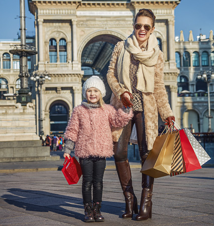 mam: Rediscovering things everybody love in Milan. Full length portrait of happy elegant mother and daughter travellers with shopping bags near Galleria Vittorio Emanuele II in Milan, Italy