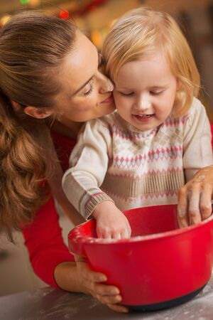 smeared baby: flour smeared mother and baby making christmas cookies Stock Photo
