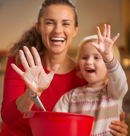 smeared baby: Closeup on mother and baby hands smeared in flour