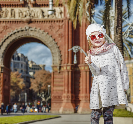in Barcelona for a perfect winter. Portrait of happy modern child in Barcelona, Spain showing thumbs up