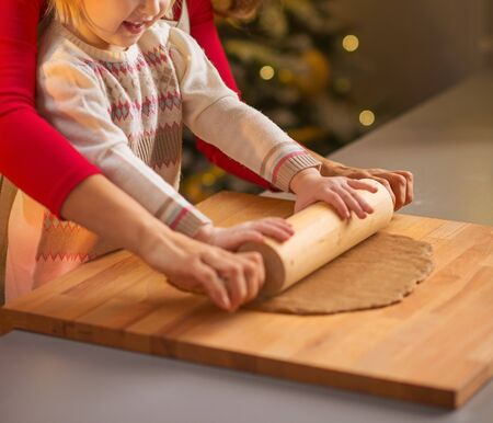 Smiling mother and baby rolling pin dough in christmas decorated kitchen Stock Photo