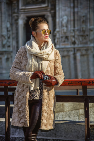 everybody: Rediscovering things everybody love in Milan. elegant woman in fur coat and sunglasses in Milan, Italy looking into the distance while holding digital photo camera Stock Photo