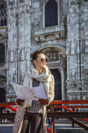 everybody: Rediscovering things everybody love in Milan. smiling young woman in fur coat and sunglasses in Milan, Italy with map looking into the distance Stock Photo