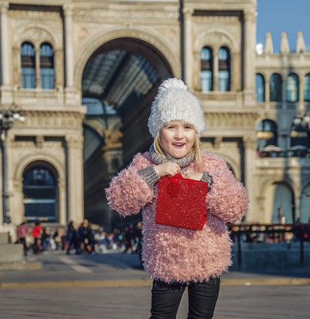 everybody: Rediscovering things everybody love in Milan. Full length portrait of surprised trendy girl with red shopping bag in Milan, Italy
