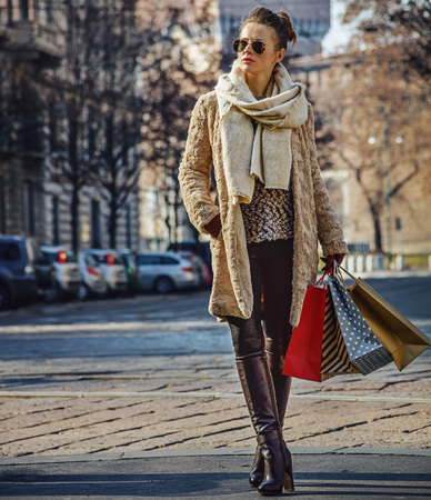 sforza: Rediscovering things everybody love in Milan. Full length portrait of elegant traveller woman in fur coat and sunglasses in Milan, Italy looking into the distance and standing