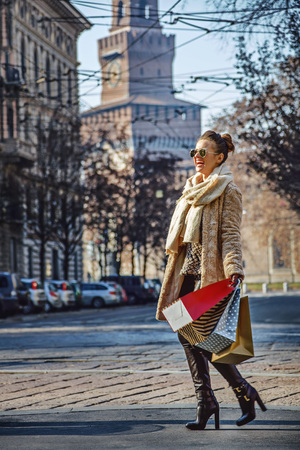 Rediscovering things everybody love in Milan. Full length portrait of cheerful trendy tourist woman in fur coat and sunglasses near Sforza Castle in Milan, Italy walking