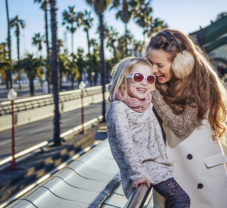 having fun in winter time: in Barcelona for a perfect winter. smiling modern mother and daughter travellers in Barcelona, Spain having fun time