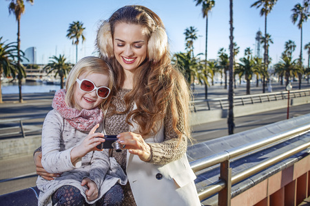winter photos: in Barcelona for a perfect winter. smiling modern mother and daughter travellers in Barcelona, Spain viewing photos on camera