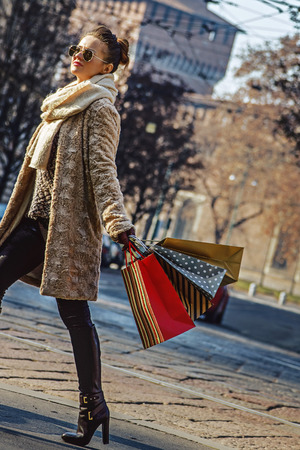 sforza: Rediscovering things everybody love in Milan. Full length portrait of young woman with shopping bags in Milan, Italy walking