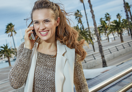 in Barcelona for a perfect winter. happy trendy tourist woman  in Barcelona, Spain speaking on a cell phone