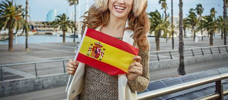 in Barcelona for a perfect winter. smiling trendy tourist woman in earmuffs on embankment in Barcelona, Spain showing flag