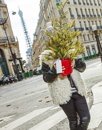 Boiling hot trendy winter in Paris. trendy child in Paris, France hiding behind Christmas tree Stock Photo