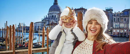 Another world vacation. smiling trendy mother and child travellers in Venice, Italy taking selfie while in Venetian mask Stock Photo
