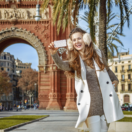 in Barcelona for a perfect winter. Full length portrait of happy young woman in earmuffs in Barcelona, Spain with mobile phone taking selfie Stock Photo