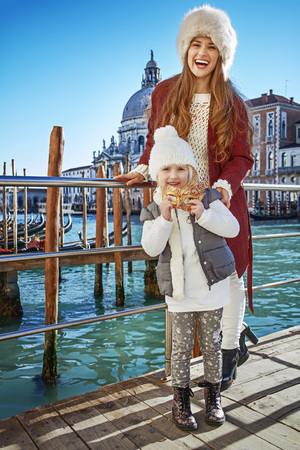 Another world vacation. Full length portrait of happy young mother and child travellers in Venice, Italy holding Venetian mask Stock Photo