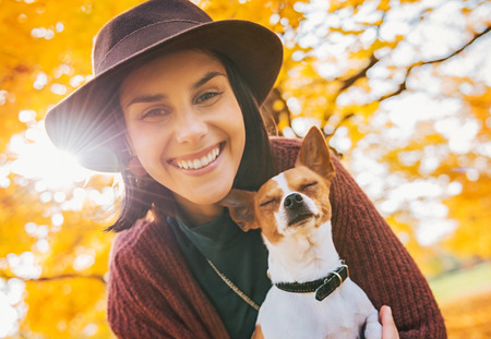 happy young woman with dog outdoors in autumn Reklamní fotografie