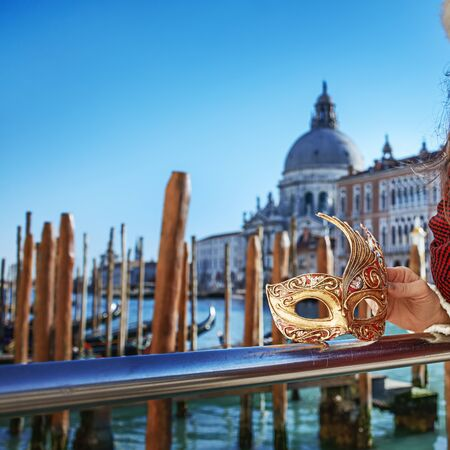 Another world vacation. Closeup on Venetian mask in hand of young  woman in fur hat on embankment in Venice, Italy Stock Photo
