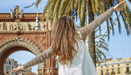 parapet: in Barcelona for a perfect winter. Seen from behind cheerful young fashion-monger in earmuffs in Barcelona, Spain walking on a parapet
