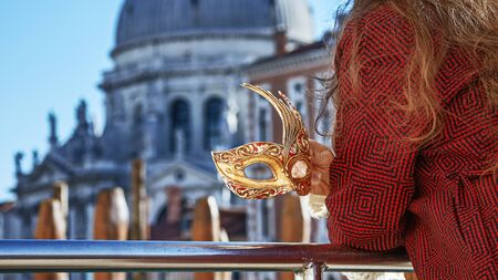 Another world vacation. Closeup on elegant Venetian mask in hand of woman in fur hat on embankment in Venice, Italy
