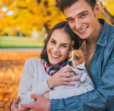 stroll: Portrait of happy young couple with dog outdoors in autumn Stock Photo