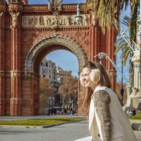 in Barcelona for a perfect winter. smiling trendy woman in earmuffs near Arc de Triomf in Barcelona, Spain looking into the distance while sitting on a parapet