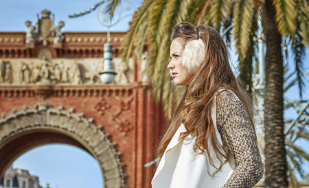 in Barcelona for a perfect winter. modern fashion-monger in earmuffs near Arc de Triomf in Barcelona, Spain looking into the distance Stock Photo