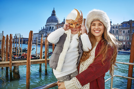 Another world vacation. Portrait of smiling modern mother and child tourists in Venice, Italy wearing Venetian mask Stock Photo