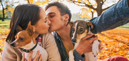 Portrait of young happy couple with two cute dogs making selfie while kissing in autumn park photo