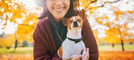 秋の屋外犬と一緒に幸せな若い女にクローズ アップ
