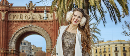 in Barcelona for a perfect winter. happy young fashion-monger in earmuffs near Arc de Triomf in Barcelona, Spain