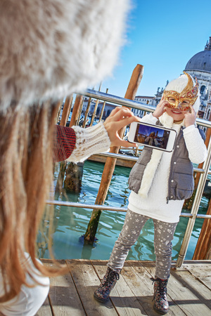 Another world vacation. modern mother in Venice, Italy taking photo of child wearing Venetian mask