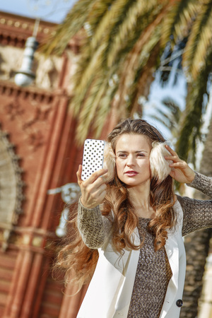in Barcelona for a perfect winter. Portrait of young woman in earmuffs near Arc de Triomf in Barcelona, Spain with smartphone taking selfie Stock Photo