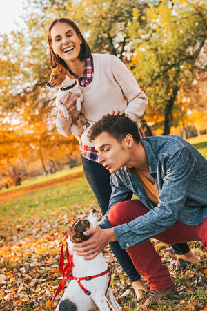 Happy young relaxed couple walking in autumn park and playing with dogs photo